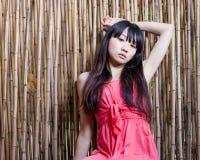 Fille asiatique par la barrière en bambou Photo stock