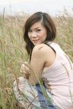 Fille asiatique parmi l'herbe Photo stock