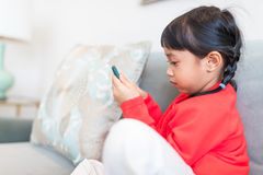 Fille asiatique regardant le téléphone intelligent et s'asseyant sur le sofa photographie stock libre de droits