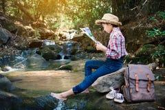 Fille asiatique regardant une carte se reposant sur la roche près de la cascade à l'arrière-plan de forêt Images libres de droits