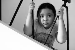 Fille asiatique s'asseyant sur le plancher à la maison Intimidation et isolement concentrés Image stock