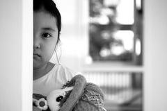 Fille asiatique s'asseyant sur le plancher à la maison Intimidation et isolement concentrés Photo libre de droits