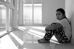 Fille asiatique s'asseyant sur le plancher à la maison Intimidation et isolement concentrés Photos libres de droits