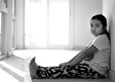 Fille asiatique s'asseyant sur le plancher à la maison Intimidation et isolement concentrés Photographie stock