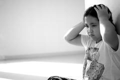 Fille asiatique s'asseyant sur le plancher à la maison Intimidation et isolement concentrés Images stock