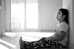 Fille asiatique s'asseyant sur le plancher à la maison Intimidation et isolement concentrés Photographie stock libre de droits