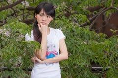 Fille asiatique se tenant parmi des feuilles Images libres de droits