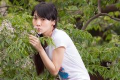 Fille asiatique se tenant parmi des feuilles Photos libres de droits