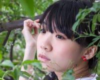 Fille asiatique se tenant parmi des feuilles Photo stock