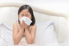 Fille asiatique soufflant le nez par le tissu photos libres de droits