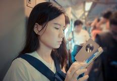 Fille asiatique soumise à une contrainte à l'aide d'un smartphone dans l'AMO de masse de transit rapide Images libres de droits