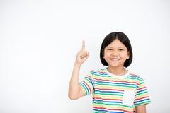 Fille asiatique souriant et dirigeant le doigt  photo stock