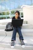 Fille asiatique sur l'ordinateur portatif à l'école image libre de droits