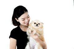 Fille asiatique tenant le chien de Pomeranian, d'isolement sur le fond blanc Photo stock
