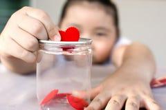 Fille asiatique tenant le foyer dans le lov en verre d'économies de concept de tirelire Images stock