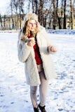 Fille assez adolescente de hippie de jeunes extérieure en parc de neige d'hiver ayant le café potable d'amusement, réchauffant le Photo stock