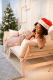 Fille assez africaine de jeunes se trouvant sur le sofa et parlant au téléphone près de l'arbre de Noël image stock