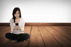Fille assez asiatique à l'aide du téléphone portable sur le plancher en bois Photo stock