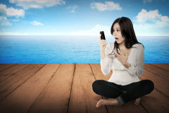 Fille assez asiatique à l'aide du téléphone portable sur le plancher en bois Images libres de droits