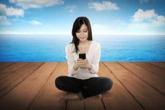 Fille assez asiatique à l'aide du téléphone portable sur le plancher en bois Images stock