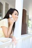 Fille assez asiatique au téléphone à la maison images stock