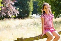 Fille assez asiatique s'asseyant sur la barrière In Countryside Image stock