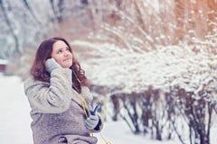 Fille assez attirante écoutant la musique sur des écouteurs en parc, appréciant le jour d'hiver Images libres de droits