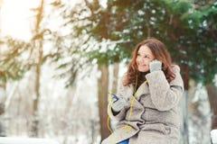 Fille assez attirante écoutant la musique sur des écouteurs en parc, appréciant le jour d'hiver Photo libre de droits