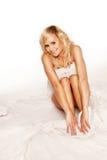 Fille assez blonde avec des bras autour de ses genoux Photographie stock libre de droits