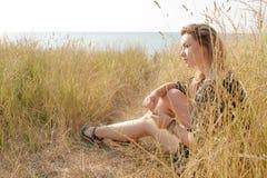 Fille assez blonde détendant sur le champ avec l'herbe sèche Image libre de droits