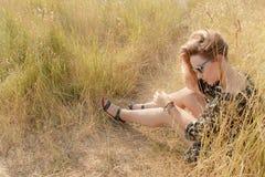 Fille assez blonde détendant sur le champ avec l'herbe sèche Photos stock