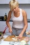 Fille assez blonde dans la cuisine effectuant des pâtes image libre de droits