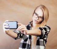 Fille assez blonde de hippie de jeunes faisant le selfie sur le fond brun chaud, concept de personnes de mode de vie Photo stock
