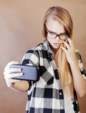 Fille assez blonde de hippie de jeunes faisant le selfie sur le fond brun chaud, concept de personnes de mode de vie Image stock