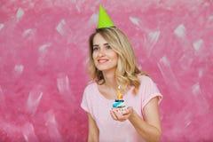 Fille assez blonde en petit gâteau de prise de chapeau d'anniversaire avec la bougie Photographie stock