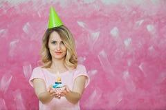 Fille assez blonde en petit gâteau de prise de chapeau d'anniversaire avec la bougie Images stock