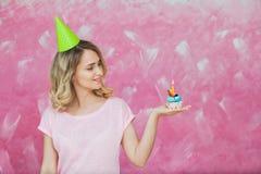 Fille assez blonde en petit gâteau de prise de chapeau d'anniversaire avec la bougie Photo stock
