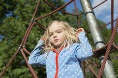 Fille assez blonde jouant sur la corde du Web rouge en été Images stock