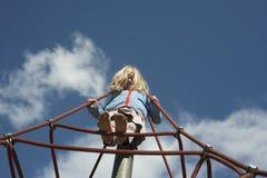 Fille assez blonde jouant sur la corde du Web rouge en été Photographie stock libre de droits
