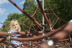 Fille assez blonde jouant sur la corde du Web rouge en été Image libre de droits
