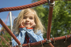 Fille assez blonde jouant sur la corde du Web rouge en été Images libres de droits