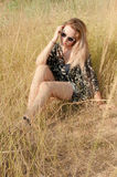 Fille assez blonde s'asseyant sur le champ avec l'herbe sèche Images stock