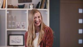 Fille assez caucasienne posant à l'appareil-photo Belle jeune dame blonde avec de longs cheveux riant gaiement à la maison 4K banque de vidéos