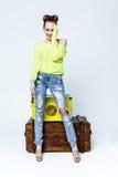 Fille assez espiègle dans des vêtements colorés par les coffres en bois Image stock