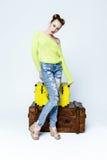 Fille assez espiègle dans des vêtements colorés par les coffres en bois Photo libre de droits