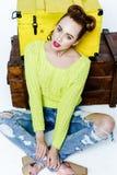 Fille assez espiègle dans des vêtements colorés par les coffres en bois Photographie stock libre de droits