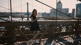 Fille assez européenne de jeunes regardant autour de, utilisant le smartphone APP le pont de Brooklyn, vue étonnante 4K de rive d banque de vidéos