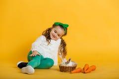 Fille assez heureuse d'enfant avec des carottes et son lapin coloré d'ami petit, concept de vacances de Pâques d'isolement sur le Photos stock