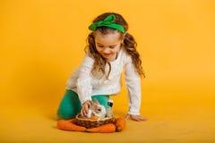 Fille assez heureuse d'enfant avec des carottes et son lapin coloré d'ami petit, concept de vacances de Pâques d'isolement sur le Images libres de droits