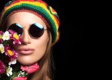 Fille assez hippie dans des lunettes de soleil avec des fleurs Photographie stock libre de droits